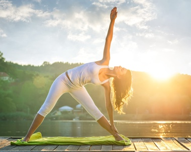 Woman doing yoga pose in front of sunset